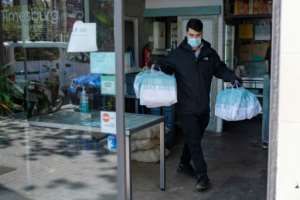 A delivery man leaves a restaurant with food for health workers in Barcelona. By Josep LAGO (AFP)