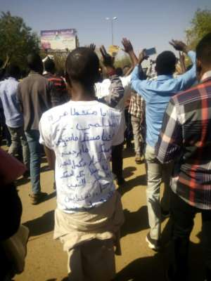 A demonstrator wearing a shirt that in Arabic reads