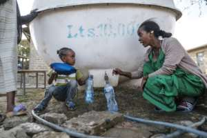 A displaced woman and child collect water from a tank at a school where they are sheltering.  By EDUARDO SOTERAS (AFP)