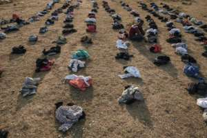 A displaced person sits among piles of clothes being distributed at the camp in Chagni.  By EDUARDO SOTERAS (AFP)