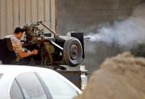A fighter fires a heavy weapon mounted on a truck towards fighters loyal to the self styled Libyan National Army in clashes south of Tripoli on Tuesday.  By Mahmud TURKIA (AFP)