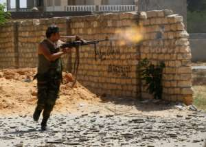 A fighter loyal to the internationally recognised Libyan Government of National Accord trades fire with forces loyal to strongman Khalifa Haftar in the capital Tripoli's suburb of Ain Zara. The photo was taken in September last year.  By Mahmud TURKIA (AFP/File)