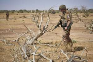 A French soldier on an exercise in Burkina Faso uses a bomb detector as he searches for a roadside device, one of the deadliest tactics used by jihadists.  By MICHELE CATTANI (AFP)