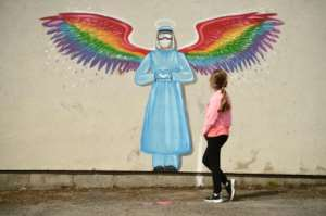 A girl looks at a mural by artist Rachel List paying tribute to NHS staff in Britain.  By Oli SCARFF (AFP)