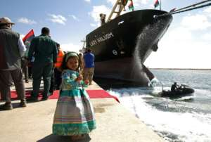 A girl poses for a photo at Benghazi port as the