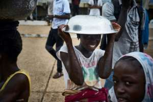 A girl poses with a metal bowl over her head on the sidelines of a protest against incumbent Malian President Ibrahim Boubacar Keita in Bamako.  By Michele CATTANI (AFP)