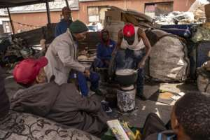 A group of reclaimers -- people who pick up and sell recyclable rubbish -- cook food at the Bekezela slum in Johannesburg. Most people here are depending on food donations to survive during the country's lockdown.  By Emmanuel Croset (AFP)