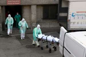 A health worker carries a body on a stretcher outside Gregorio Maranon hospital in Madrid.  By OSCAR DEL POZO (AFP)