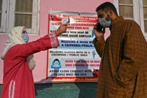 A health worker checks the temperature of a voter in India's Kashmir state.  By TAUSEEF MUSTAFA (AFP)