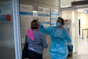 A health worker checks the temperature of a woman at the entrance of a health center in Madrid, which announced a partial lockdown for nearly a million people.  By OSCAR DEL POZO (AFP)