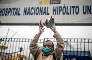 A health worker bangs a pot during a protest outside the Hipolito Unanue public hospital in Lima over the lack of protective equipment -- Peru now has more than 100,000 coronavirus cases.  By ERNESTO BENAVIDES (AFP)