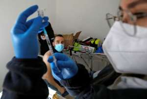 A health worker prepares a dose of the Pfizer-BioNtech vaccine on February 22, 2021 in Israel, which maintains a tight blockade on Gaza, where some 20,000 Russian-made Sputnik V vaccine doses have arrived from the United Arab Emirates.  By JALAA MAREY (AFP)