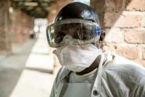 A health worker wears protective equipment as he looks on at Bikoro Hospital -- the epicenter of the latest Ebola outbreak in the Democratic Republic of Congo --  on May 12, 2018.  By MARK NAFTALIN (UNICEF/AFP/File)
