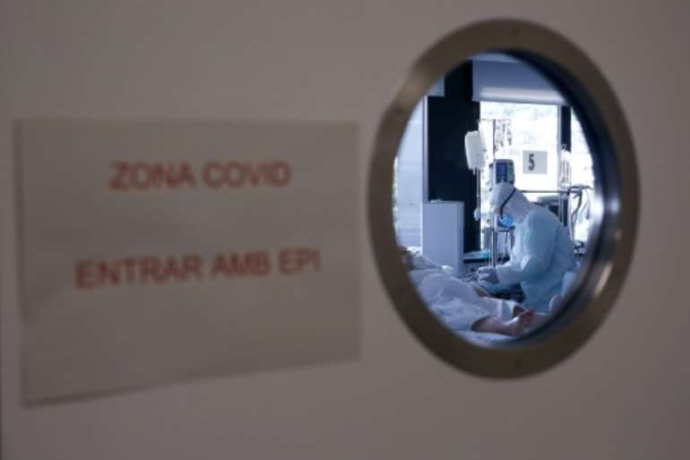 A healthcare worker in a protective suit attends to a COVID-19 coronavirus patient at a hospital in Barcelona.  By Pau Barrena (AFP)
