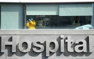 A healthcare worker looks out the window of La Paz hospital, in Madrid, as Spain's health minister calls on residents of the city to limit their movements and social contacts to the