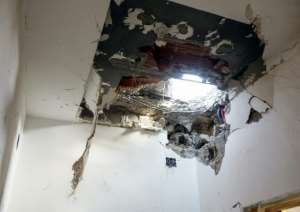 A hole in the ceiling of a house hit by a rocket in Ayn Zarah on the outskirts of the Libyan capital Tripoli, on September 4, 2018.  By Mahmud TURKIA (AFP)