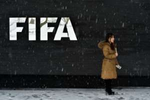 A journalist stands under the snow next to a logo of the International Federation of Association Football (FIFA) at the FIFA headquarters in Zurich, during meeting of the FIFA's governing council on January 10, 2017