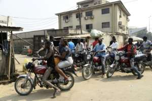 A lady rides on the back of a motorbike taxi in Lagos despite a ban on their use.  By PIUS UTOMI EKPEI (AFP)