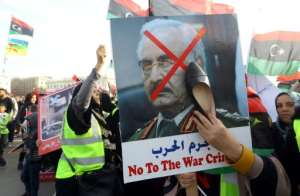 A Libyan woman hits a portrait of strongman Khalifa Haftar with a shoe during a demonstration against him and French policy towards the North African country in the capital Tripoli on Friday.  By Mahmud TURKIA (AFP)