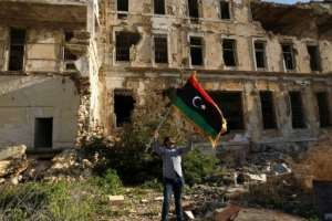 A Libyan man waves the national flag during a gathering in Benghazi to mark years since the uprising that ousted dictator Moamer Kadhafi.  By Abdullah DOMA (AFP)