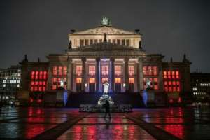 A lone pedestrian walks past the concert hall at Gendarmenmarkt illuminated in red to draw attention to the plight of cultural institutions in Berlin amid the pandemic.  By STEFANIE LOOS (AFP)