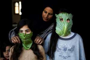 A Palestinian mother entertains her children with makeshift masks made of cabbage in Beit Lahia in the northern Gaza Strip on April 16, 2020.  By MOHAMMED ABED (AFP)
