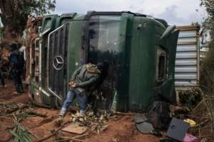 A passer-by looks inside an overturned truck in the middle of National Road 27 in Ituri.  By ALEXIS HUGUET (AFP)