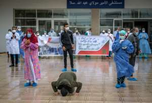 A patient who recovered from Covid-19 kisses the ground and another rejoices with medical staff as they leave a hospital in the city of Sale, north of the Moroccan capital Rabat.  By FADEL SENNA (AFP)