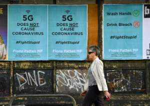 A pedestrian walks past public service announcement posters, negating a conspiracy that 5G telecommunications technology causes the coronavirus, in Melbourne, Australia.  By William WEST (AFP)