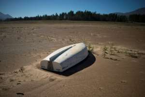 A picture taken on May 10, 2017 shows a boat lying on the sand at the Theewaterskloof Dam, which has less than 20% of it's water capacity, near Villiersdorp, about 108 km from Cape Town.  By Rodger BOSCH (AFP/File)