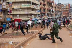 A police officer chases street vendors in Kampala, Uganda, after the public were directed to stay home for 32 days.  By Badru KATUMBA (AFP)