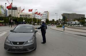 A policeman checks a vehicle in Tunis on March 24 as part of steps to contain the coronavirus.  By FETHI BELAID (AFP/File)