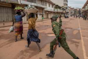 A policeman in the Ugandan capital Kampala beats an orange hawker for defying stay-at-home instructions.  By Badru KATUMBA (AFP)