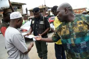 A policeman in Lagos distributes flyers about measures to prevent coronavirus.  By PIUS UTOMI EKPEI (AFP)