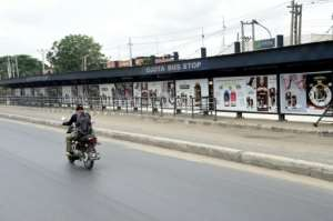 A policeman on a bike drives past a deserted bus stop.  By PIUS UTOMI EKPEI (AFP)