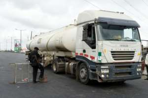 A policeman removes a road block to give access to a fuel tanker.  By PIUS UTOMI EKPEI (AFP)