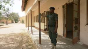A policeman stands on guard at the empty Government Girls Technical College in northern Nigerian, where 110 girls were kidnapped by Boko Haram Islamists last month
