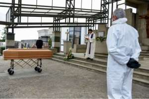 A priest reads funeral rites by a coffin in a cemetery in Grassobbio, Lombardy, Italy as pallbearers stand by.  By Piero CRUCIATTI (AFP)