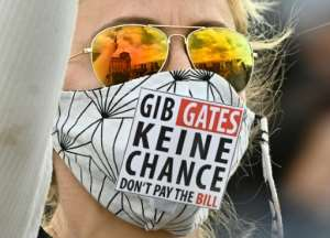 A protester at a rally in Berlin wearing a mask saying