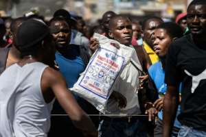 A protester holds a bag of corn meal with a price written on it. Soaring inflation and shortage of basic goods have fuelled anger.  By Zinyange Auntony (AFP)
