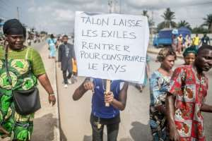 A protestor at a rally last month holds up a sign reading 'Talon, let exiled citizens return to rebuild the country'.  By Yanick Folly (AFP)