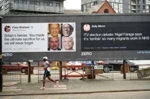 A runner passes posters critical of comments made about migrants in Manchester, north-west England.  By Oli SCARFF (AFP)