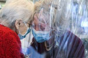 A resident at the Domenico Sartor nursing home near Venice hugs her visiting daughter through a plastic screen in a so-called