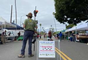 A staff member of the Mar Vista Farmer's Market makes sure people stay six feet apart from each other using a bullhorn and a 6-foot pole in Mar Vista, California.  By Chris DELMAS (AFP)