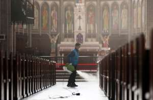 A staff member sprays disinfectant as part of preventive measures against the spread of the COVID-19 coronavirus, at Myeongdong Catholic Cathedral in Seoul.  By - (YONHAP/AFP)