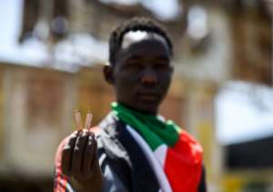 A Sudanese man holds up bullet casings at the protest site outside the army headquarters. By Mohamed el-Shahed (AFP)