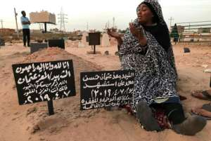 A Sudanese mother, Khadom, mourns at the grave of her son Al-Moez, who was killed when a bullet pierced the window of his workplace during anti-government demonstrations in April.  By Claire DOYEN (AFP)