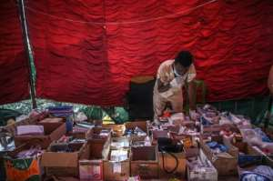 A Sudanese aid volunteer sorts through medicines inside a first aid tent during the sit-in outside army headquarters on Saturday.  By OZAN KOSE (AFP)