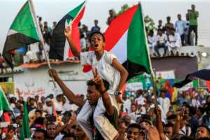 A Sudanese boy celebrates after protest leaders struck a deal with the ruling generals on a new governing body.  By ASHRAF SHAZLY (AFP)