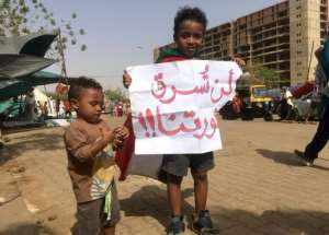 A Sudanese boy holds a sign reading in Arabic reading